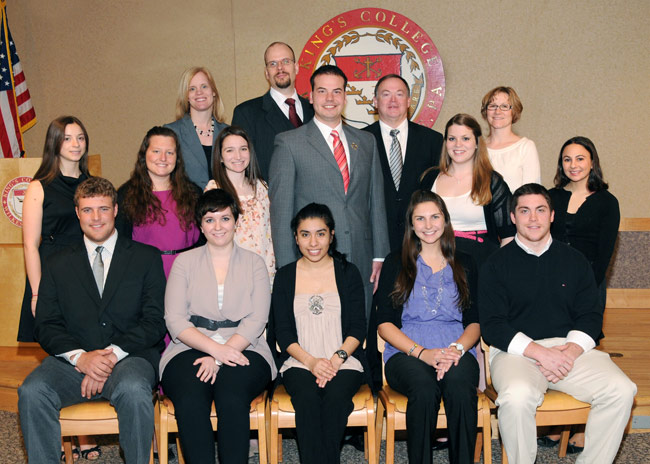 Pictured seated, from left, are student inductees Ian Oakley, Jennie Hampton, Noemi Tlatenchi, Elizabeth Demko, and Ryan Cordingly. Shown in second row, from left, are student inductees Sarah Scinto, Dawn Long, Alexandra Shinert, Anthony Scaccia, Erica Pandolfo, and Nicole Rave. Pictured in third, row, from left, are faculty and administration inductees Jill Yurko, assistant professor of education; Kyle Johnson, assistant professor of philosophy; and Robert McGonigle, associate vice president for student affairs and dean of students.  At far right is Amy Swiatek, math specialist instructor and faculty moderator for Delta Epsilon Sigma. Absent from photo are student inductees Rachael Pompeii, James Sprague and Kyley Henry and faculty and administration inductees and Dr. Maria Jump and Sheri Yech.