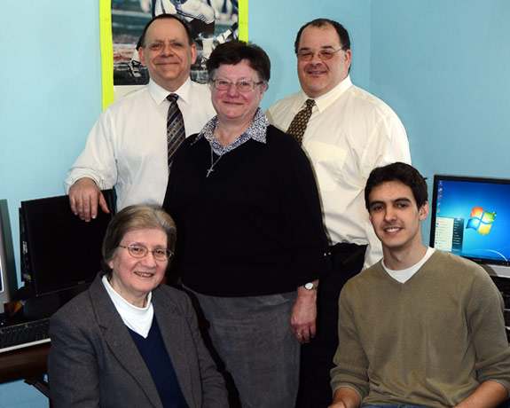 Pictured seated with some of the donated equipment is, from left: Sister Elizabeth Brody, director, Mineral Springs Center; and Timothy Mike, junior CIS major, King's. Standing: Paul Moran, executive director of IITS, King's; Sister Eleace King, director, McGlynn Learning Center; and Ray Pryor, managing director of user services, King's.