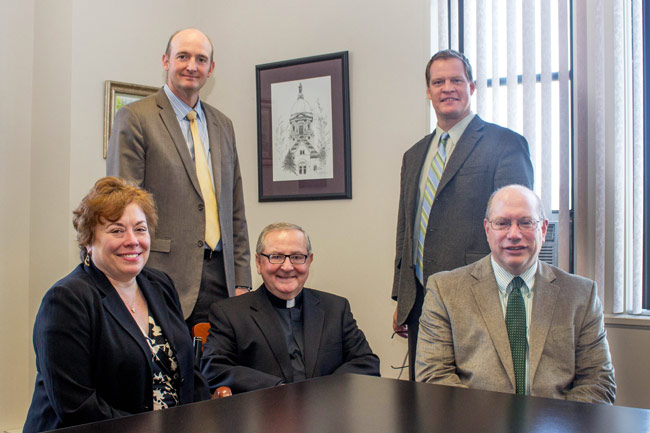 Pictured seated, from left, is Cathy Pieronek, associate dean of academic affairs, University of Notre Dame; Father John Ryan, C.S.C., president of King's College; and Paul Lamore, associate professor of management at King's and ESTEEM program coordinator. Pictured standing, from left, is Dr. Joseph Evan, vice president for academic affairs at King's, and James Anderson, executive director of admissions at King's.