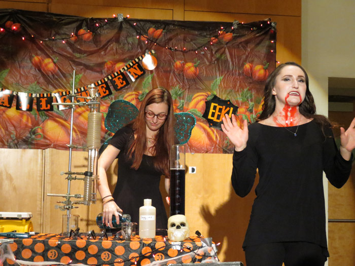 """King's College recent graduates Brittney Price and Virginie Menard conduct a luminescence demonstration as part of King's annual children's Halloween exhibition, """"Things That Go Boom in the Night."""""""