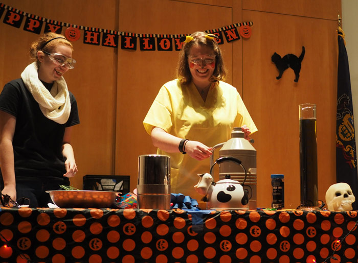 """Biochemistry major Zoe Waizenegger assists Dr. Julie Belanger, associate professor of chemistry, during King's annual Halloween exhibition for children, """"Things That Go Boom in the Night."""""""