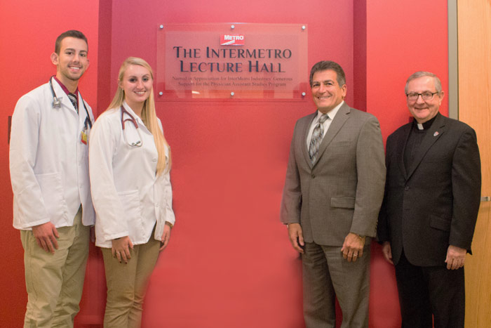 Pictured, from left, are physician assistant studies majors Brittany Arens and Nicholas Broughton, Nackley, and Father John Ryan, C.S.C., president of King's.