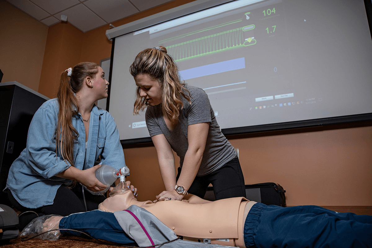 nursing students practice CPR and monitor vitals on a dummy