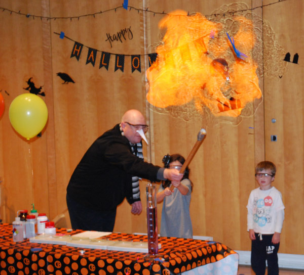 "Dr. Trent Snider, associate professor of chemistry, performs an ""exploding"" hydrogen balloon trick."
