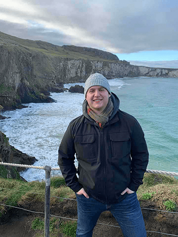 Jarett poses in front of a rocky coastline in Northern Ireland.