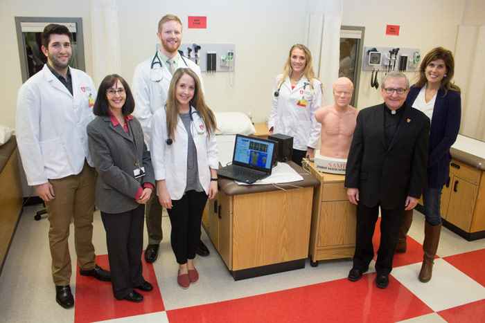 Pictured in front row, from left, is Diana Easton, director of the King's Physician Assistant Program; physician assistant major Hilary White; and Father John Ryan, C.S.C., King's president.  Pictured in back row, from left, are King's physician assistant
